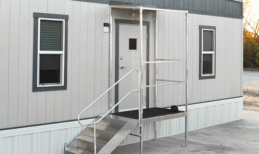 Premium entrance package with canopy and handrail outside of a mobile office trailer
